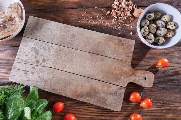 그릇, 견과류, 토마토, 고기 및 채소 조각에 삶은 메추라기 달걀 주위 식탁에 나무 보드. 공간을 복사하십시오. 건강한 샐러드 재료. 플랫 레이