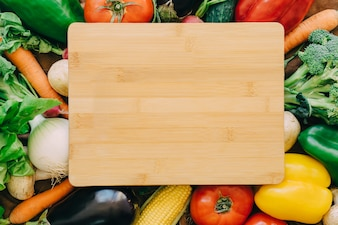 Wooden board on vegetables