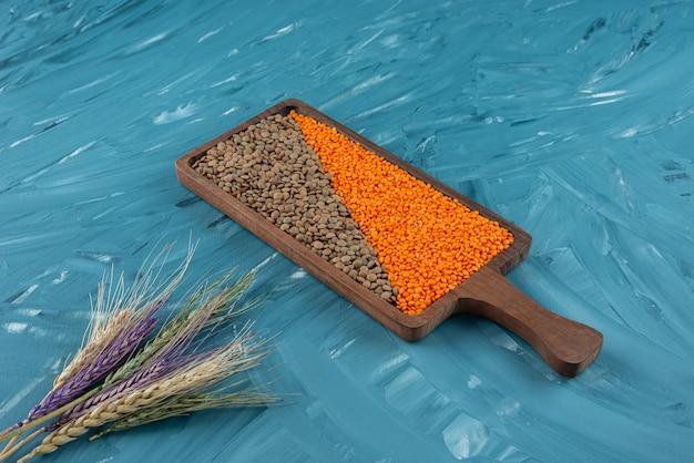 Tavola di legno di grano saraceno secco crudo e lenticchie sulla superficie blu.