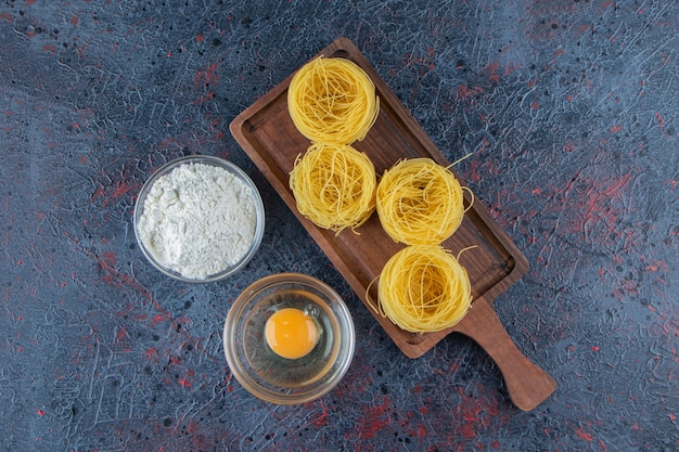 A wooden board of raw dry nest pasta with flour and uncooked egg on a dark background .