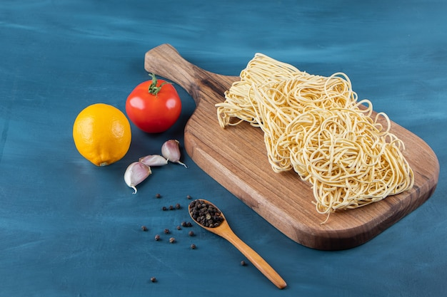 A wooden board of raw noodles with fresh red tomato and lemon on a blue background..
