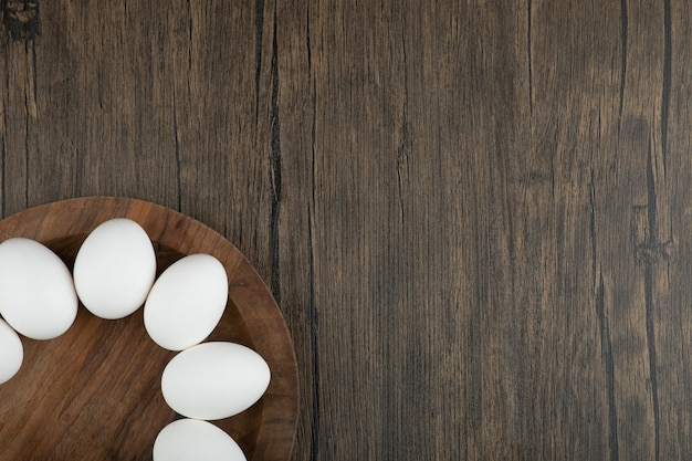 Wooden board of raw organic eggs on wooden surface.