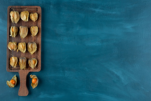 Wooden board of ripe kumquats with leaves on blue background.