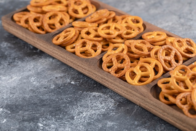 A wooden board of salty dry pretzels cracker placed on a stone surface