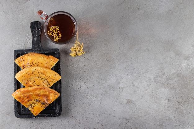 Tavola di legno di pasticceria fresca a fette e bicchiere di tè sulla superficie in marmo