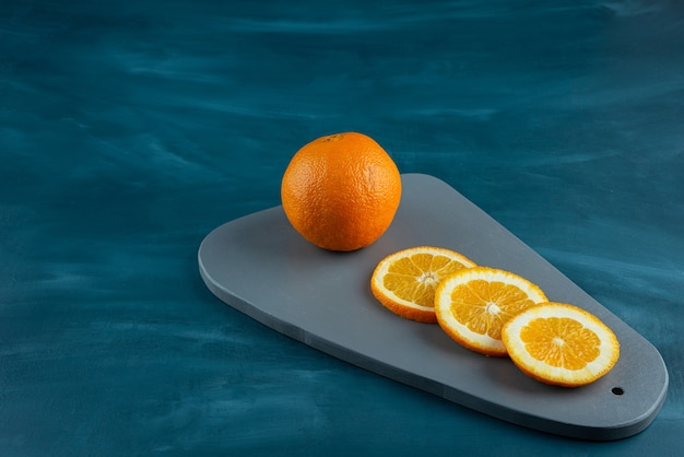Wooden board of sliced juicy oranges on blue surface.