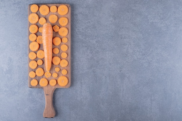 A wooden board of sliced and whole carrots , on the marble background.