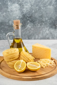 Wooden board of spaghetti nests, oil, lemonnd cheese on white table.