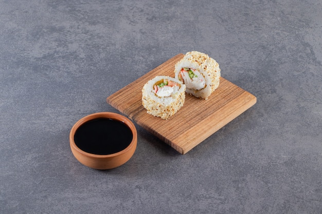 Wooden board of sushi rolls with sesame seeds on stone background.