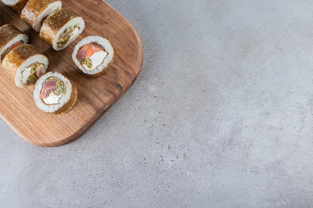 Wooden board of sushi rolls with tuna fish on stone background.