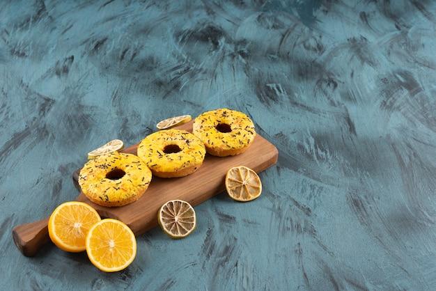 Una tavola di legno di ciambelle dolci con limone fresco a fette e fette secche