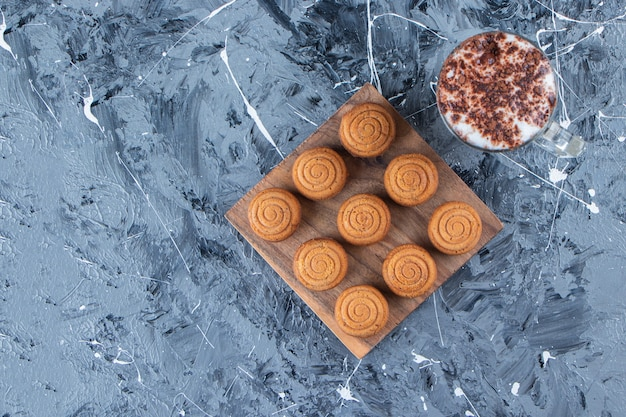 A wooden board of sweet round cookies with a glass cup of tasty hot coffee on a marble background.