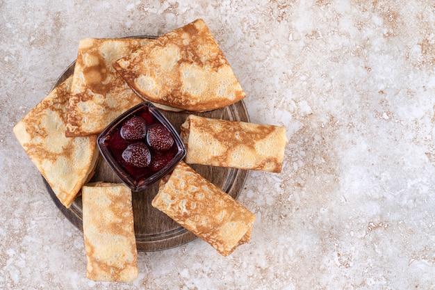 Una tavola di legno di gustose crepes e marmellata di fragole