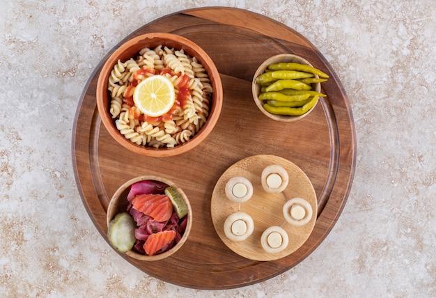 Una tavola di legno di gustosa pasta con funghi e spezie