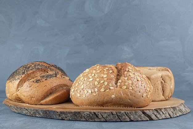 Tavola di legno sotto tre pagnotte di pane sul tavolo di marmo.