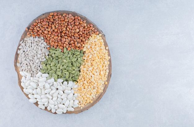 Деревянная доска, покрытая красной фасолью, пепитасом, синей фасолью, красной чечевицей и очищенными семенами подсолнечника на мраморной поверхности