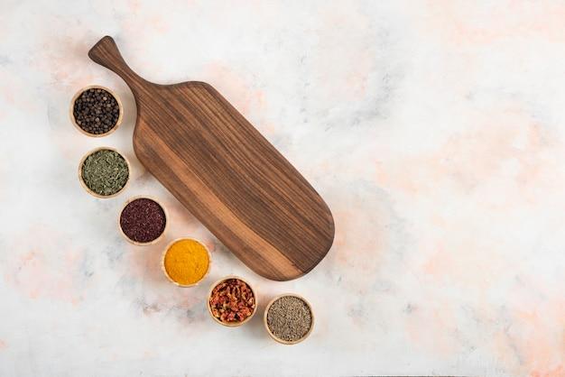 Tavola di legno e vari tipi di spezie su sfondo bianco.