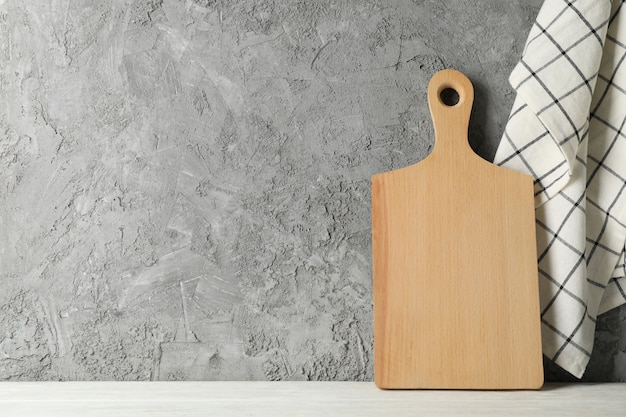 Wooden board on white table against gray background, space for text