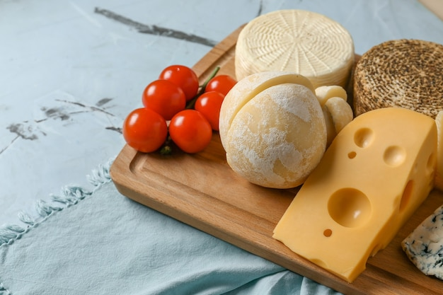 Wooden board with assortment of tasty cheese on table