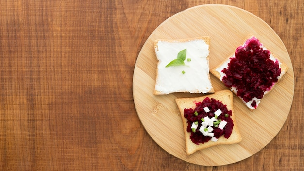 Wooden board with beetroot and cheese sandwich
