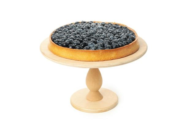 Деревянная доска с черничным пирогом, изолированным на белом столе