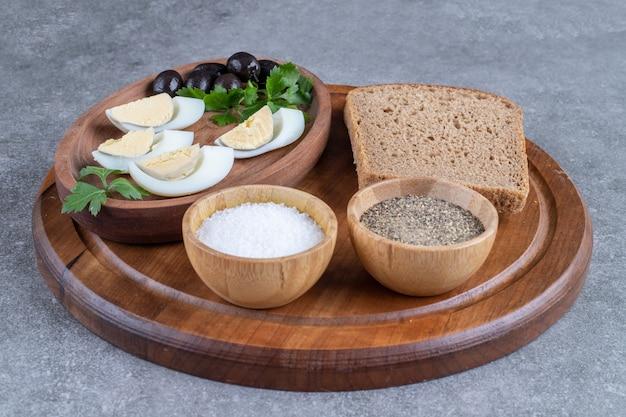Una tavola di legno con uova sode e fetta di pane. foto di alta qualità