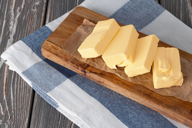 Wooden board with butter on blue checkered napkin