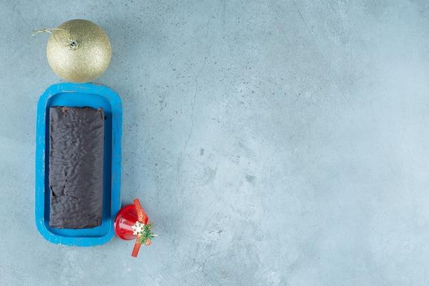 Una tavola di legno con rotolo di torta al cioccolato con giocattoli di natale.