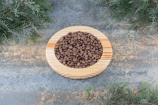 A wooden board with coffee beans on marble background. high quality photo
