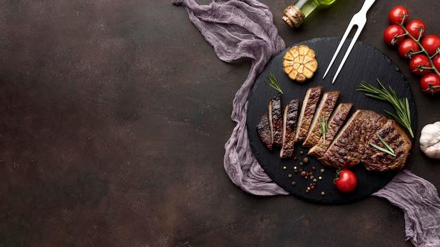 調理された肉とコピースペースを持つ木の板