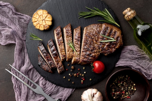Wooden board with cooked meat on desk