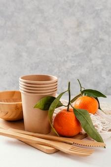 Деревянная доска со столовыми приборами и мандаринами
