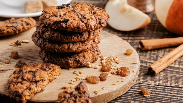 Wooden board with delicious cookies on table