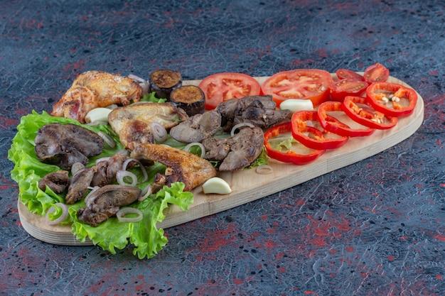 Una tavola di legno con cibo delizioso su una superficie di marmo