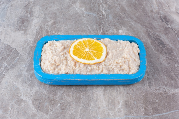 A wooden board with delicious oatmeal and a slice of orange fruit.