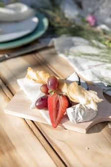 さまざまな種類のチーズとフルーツが入った木の板