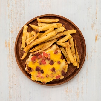 Wooden board with french fries and omelette on painted desk
