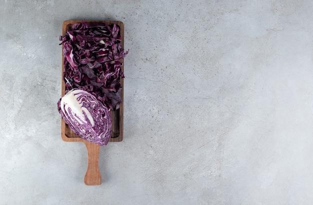 Una tavola di legno con cavolo viola affettato fresco. foto di alta qualità