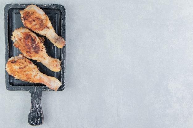 Una tavola di legno con carne di cosce di pollo fritte.