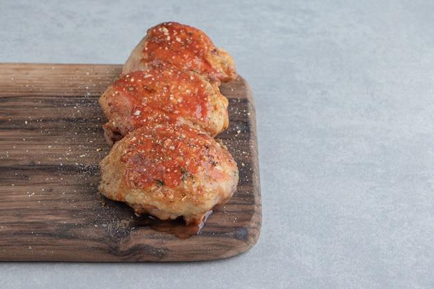 Una tavola di legno con carne di pollo fritta deliziosa.