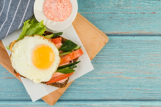 Wooden board with fried egg with vegetables sandwich