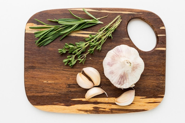 Wooden board with garlic and dill
