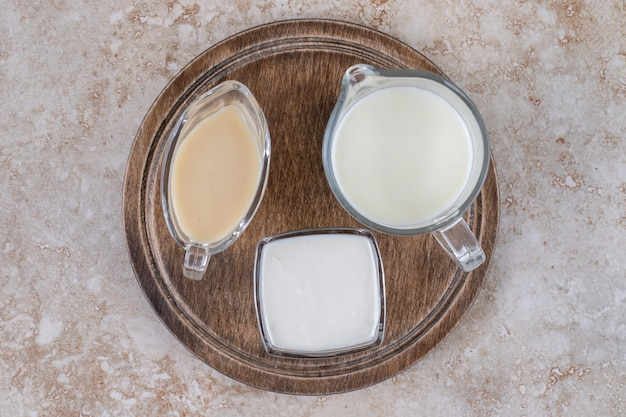 A wooden board with glass cups of milk