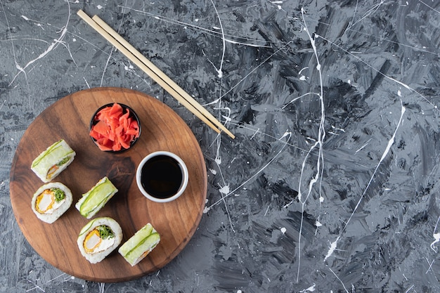 Wooden board with green dragon sushi rolls on marble background.