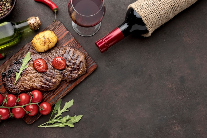 Wooden board with grilled meat with copy-space