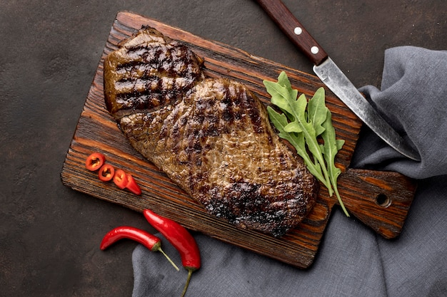 Wooden board with grilled meat