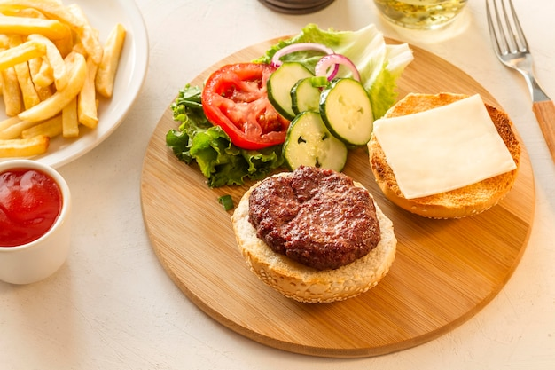 Wooden board with hamburger and fries