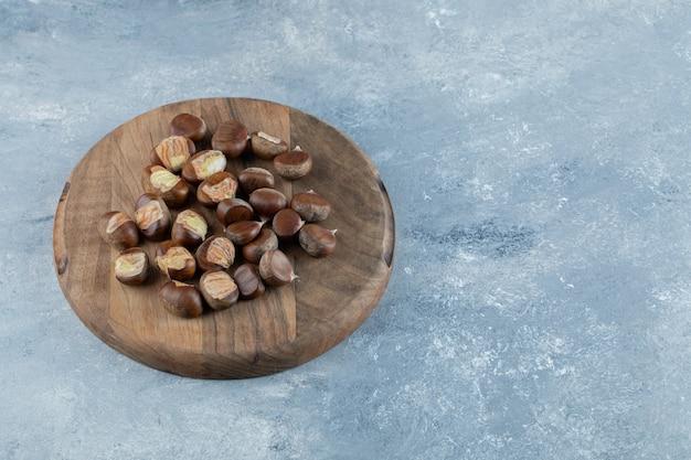 Una tavola di legno con castagne sane su uno sfondo grigio.