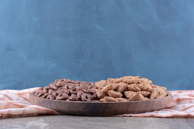 A wooden board with healthy chocolate cereal rings and chocolate pads corn flakes.