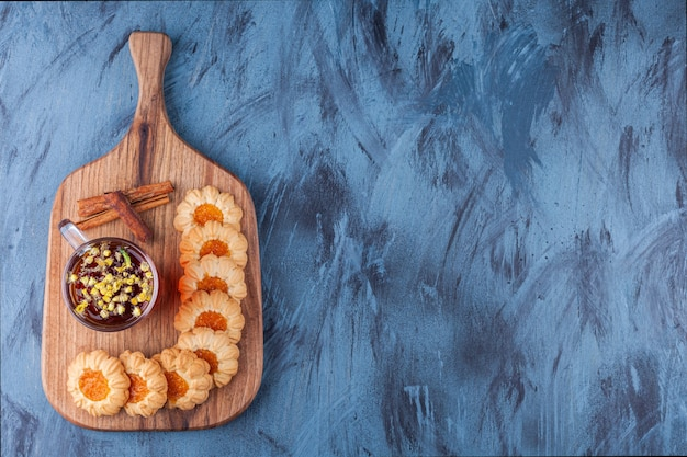 Wooden board with jelly cookies and cup of tea on blue background.